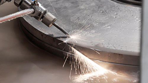 Close-up of waterjet cutting metal material, causing sparks. Flow has multi-axis cutting for production requirements.