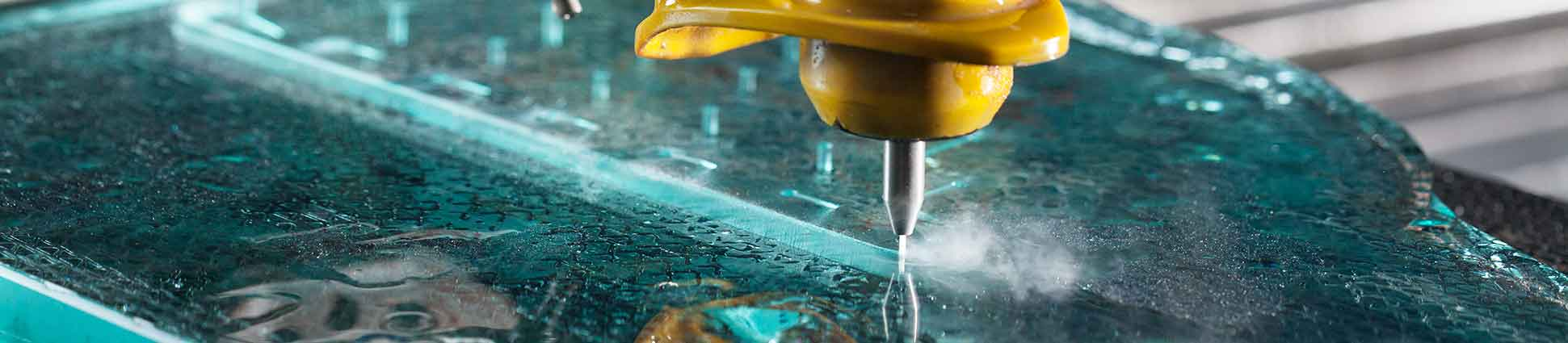 Close up of waterjet with yellow shield cutting in a straight line on blue glass material