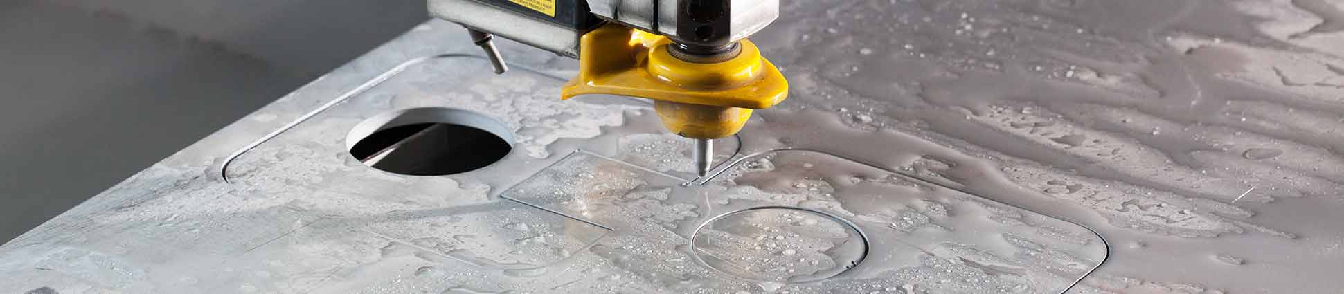 Waterjet with yellow spray shield, cutting geometric pattern on metal material
