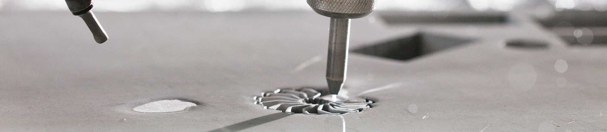 Flow waterjet cutting cylindrical metal part with blades spiraling out from center.