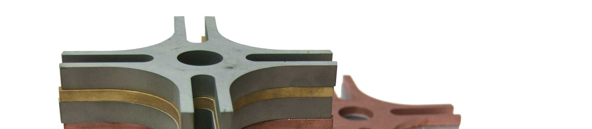Top view of a variety of waterjet cut materials, cut in the same pattern and stacked vertically