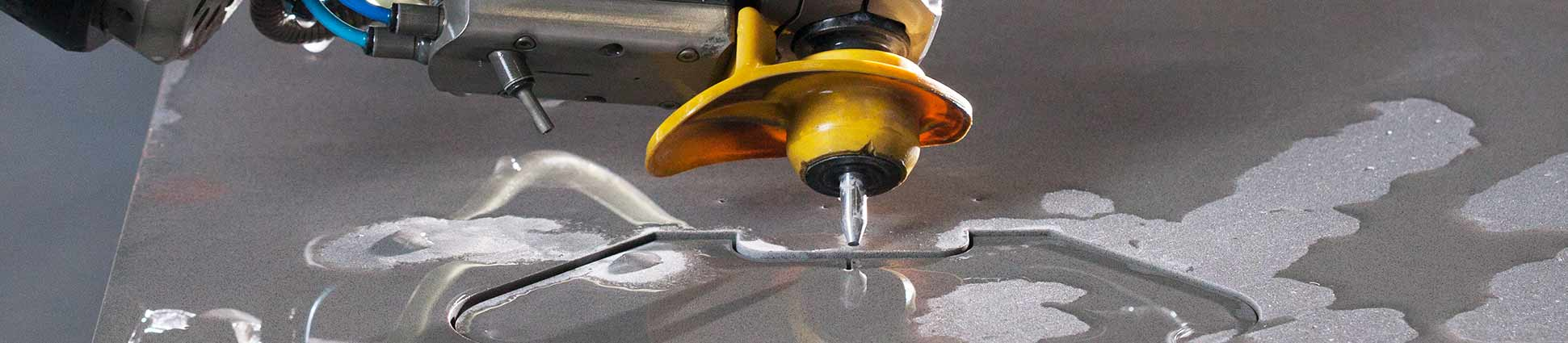 Waterjet cutting head tilted towards the background, cutting gray colored stone material