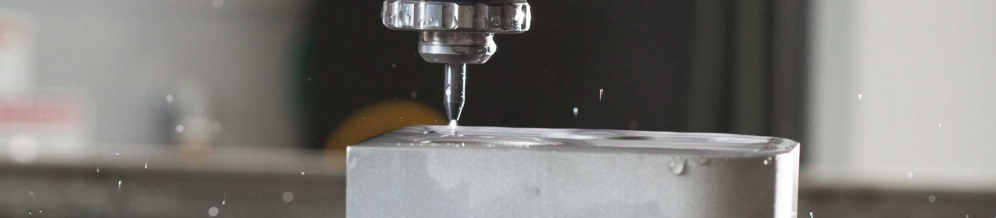 Close up of Flow waterjet cutting thick metal material.